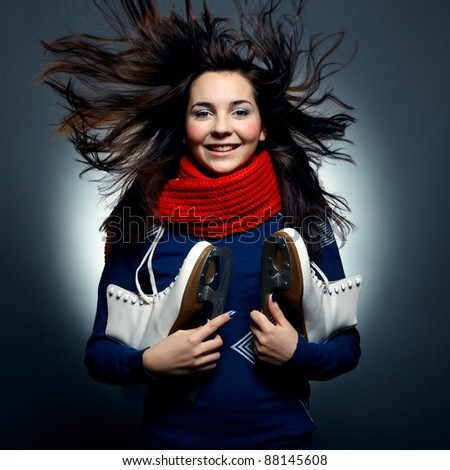 Fashion photo of beautiful woman with magnificent hair. Pretty young smiling girl with the skates - stock photo