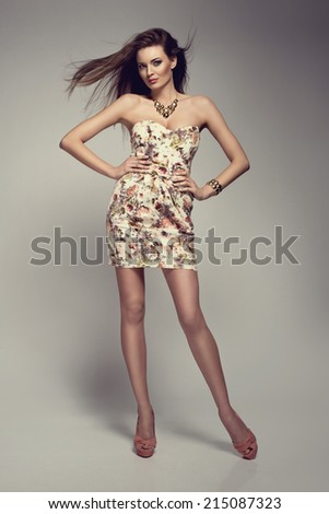 Fashion photo of beautiful young brunette woman in flower pattern dress  - stock photo
