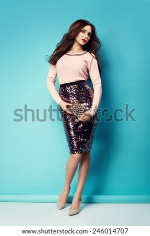 fashion photo of beautiful young woman in nice clothes and small hand purse. Red lips  - stock photo