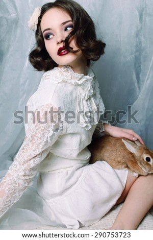 Fashion photo of beautiful young woman with curly hair wearing a retro style in white lace dress, pointe shoes, holing a rabbit and posing at studio - stock photo