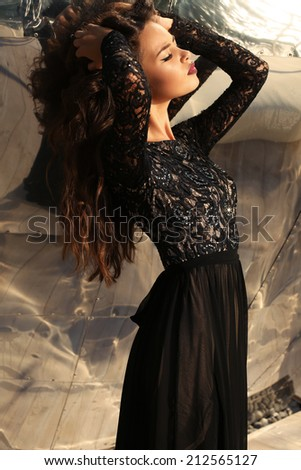 fashion photo of beautiful young woman with long dark hair in elegant black dress posing beside a metallic wall - stock photo