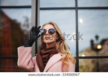 Fashion photo of beautiful young  woman with sunglasses. City lifestyle. Female fashion. Close up portrait. Beautiful reflection background  - stock photo