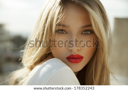 Fashion photo of blonde beauty with natural make up and red lipstick. horizontal, outdoors shot.  - stock photo