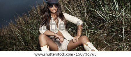 Fashion photo of brunette young woman posing with sunglasses. - stock photo