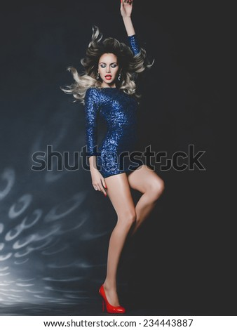 Fashion photo of dancing gorgeous woman in sequined dress - stock photo