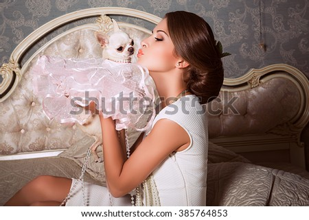 fashion photo of elegant and sexy woman in white clothes and chihuahua dog,  with beautiful hairstyle posing at bedroom with classic interior - stock photo