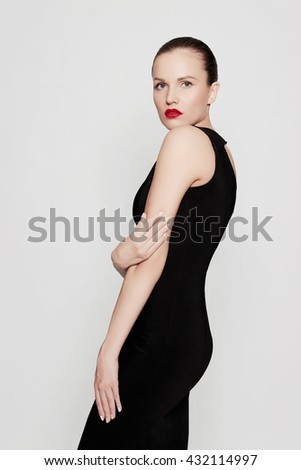 fashion photo of glamor beautiful young woman in a black sexy dress posing in the studio,luxury.beauty brunette girl with red lips - stock photo