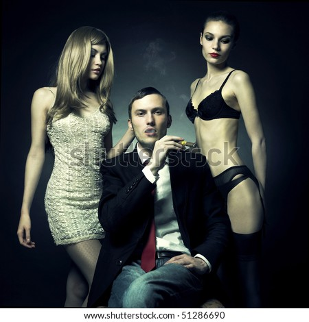 Fashion photo of handsome man and two women - stock photo