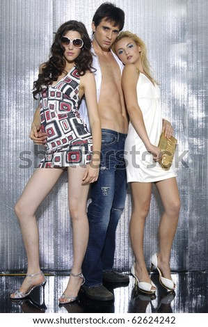 Fashion photo of handsome man and two women shot in studio - stock photo