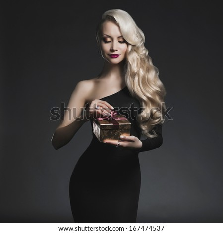 Fashion photo of luxury blonde with Christmas gift - stock photo