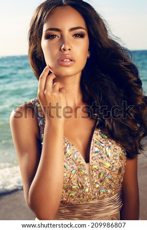 fashion photo of sensual beautiful woman with dark hair in luxurious sequin dress posing on summer beach in sunlight rays - stock photo