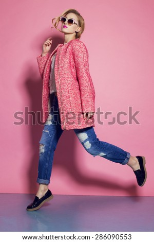 Fashion photo of sexy beautiful woman with blond curly hair, bright makeup wearing a red coat,blue jeans moving on a pink background  - stock photo