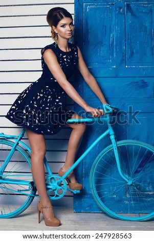 fashion photo of sexy brunette woman in evening black dress,accessories with beautiful hairstyle and long slim legs posing on a bike near the blue door  - stock photo