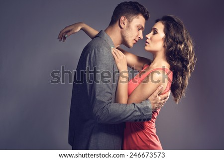 Fashion photo of sexy elegant couple in the tender passion. Studio portrait - stock photo