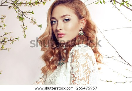 Fashion photo of sexy girl with curly hair wearing a lace dress,beautiful earrings and necklace,posing at sunny garden around flowering trees - stock photo