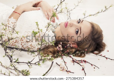 Fashion photo of sexy girl with curly hair wearing a lace dress,beautiful earrings and necklace,posing at studio around flowering trees - stock photo