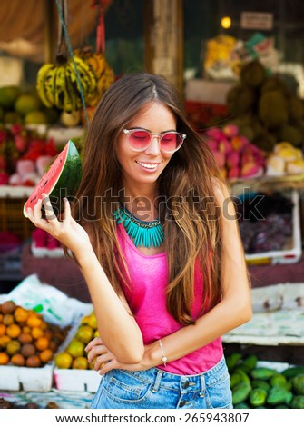 Fashion photo of sexy glamour model,with dark hair in glasses,eating fresh fruits,near fruit market.Wear fashion,colorful clothes and cool glasses. Having fun and  smiling. Fashion outdoor portrait. - stock photo