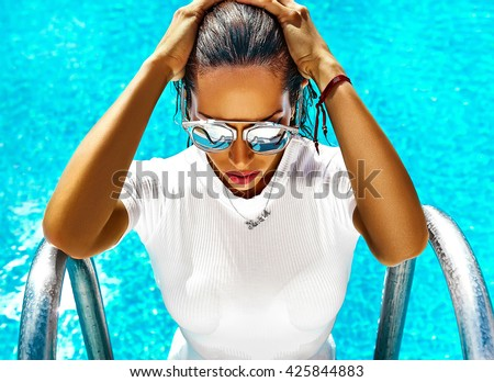 fashion photo of sexy hot beautiful girl model with dark hair in white swimwear coming out of swimming pool in sunglasses and touching her hair - stock photo