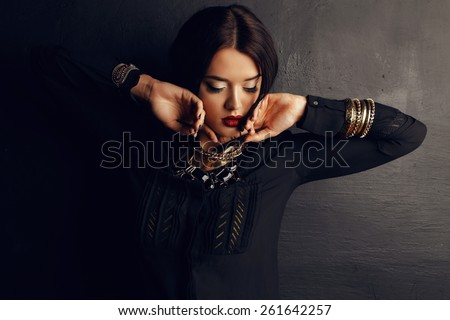 Fashion photo of sexy Indian woman with dark hair and bright make-up wearing black shirt and  luxurious gold necklace,bracelets, earrings posing at studio - stock photo