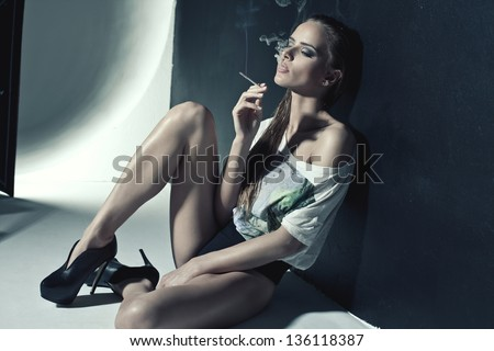 Fashion photo of sexy woman smoking a cigarette - stock photo