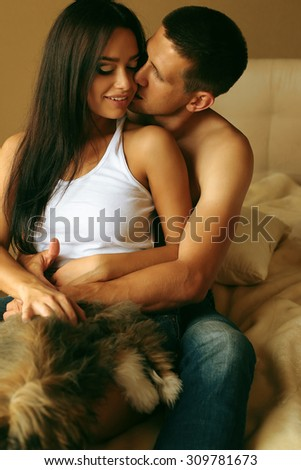 Fashion photo of two young beautiful lovers wearing a jeans relaxing and hugging on a bed with little cute dog - stock photo
