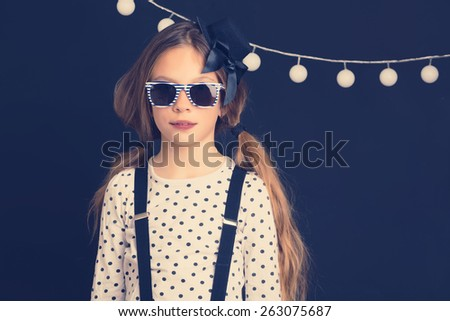 Fashion photo of young hipster child wearing cool clothes and sunglasses standing over dark wall, instagram toned image - stock photo