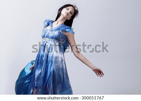 Fashion photo of young magnificent woman in blue dress. Studio portrait - stock photo