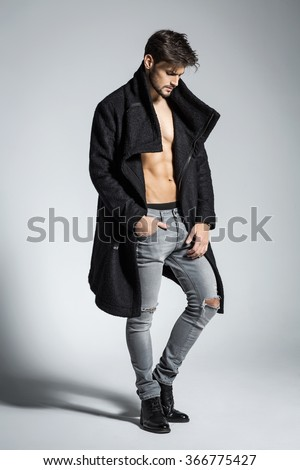 Fashion photo of young male model in black coat - stock photo
