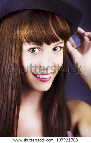 Fashion photo on the face of beautiful smiling woman with a black hat on head - stock photo