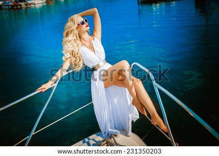 Fashion photo sexy woman blonde relaxing on yacht, vogue style model, luxury lifestyle woman, fashionable girl at vacation, alluring tanned girl, Monaco, series, soft sunset focus - stock photo