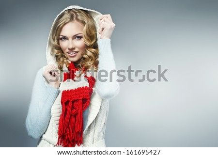 fashion picture of beautiful smiling blonde woman wearing a woolen sweater and knitted scarf - stock photo