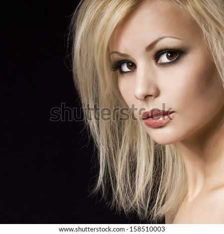 Fashion portrait. Beautiful blonde woman with professional makeup, over black background. Vogue style model - stock photo