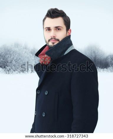Fashion portrait handsome bearded man wearing black coat in winter day - stock photo