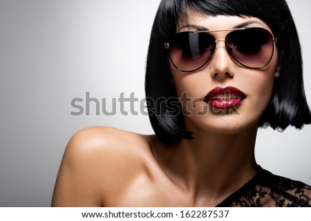 Fashion portrait of a  beautiful brunette woman with shot hairstyle with red sunglasses - studio photo - stock photo