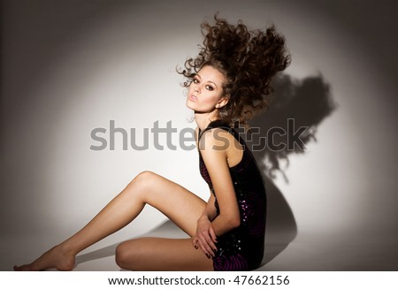 Fashion Portrait of a beautiful young sexy woman posing on gray background - stock photo