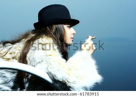Fashion portrait of a beautiful young sexy woman wearing fur coat - stock photo