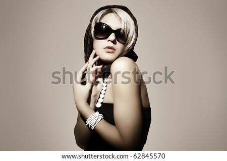 Fashion portrait of a beautiful young sexy woman wearing sunglasses - stock photo