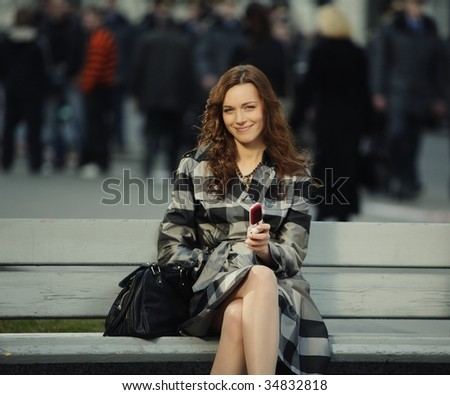 fashion portrait of a beautiful young woman with a mobile phone - stock photo