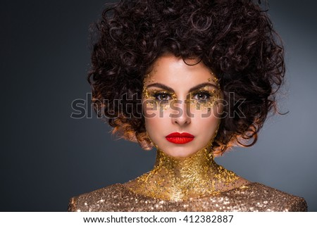 Fashion portrait of a caucasian brunette with beautiful eyes. Bright make-up: red lipstick, black eyeliner and special golden elements on her skin. Woman's relaxed face in foreground. - stock photo