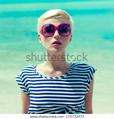 fashion portrait of a girl on a background of the sea - stock photo