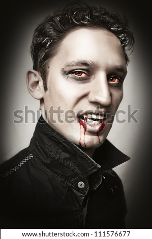 Fashion portrait of a handsome young man with vampire style bangs, blood and  make-up. studio shot. - stock photo