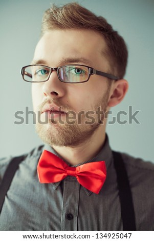 Fashion portrait of a man with red bowtie and glasses (hipster style) - stock photo