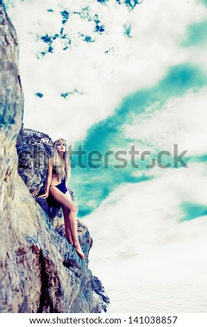 fashion portrait of a sensual blonde on a  stones - stock photo