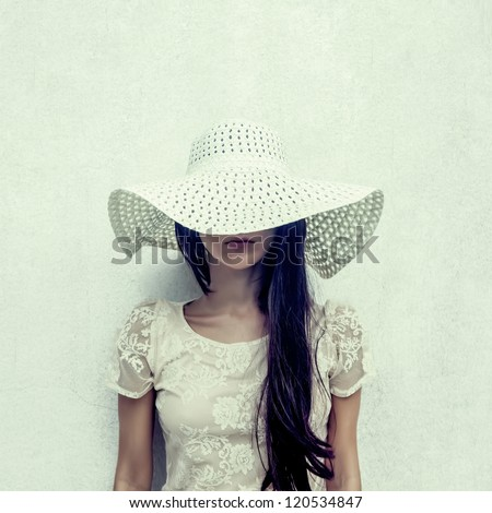 fashion portrait of a sensual girl in a hat against the wall - stock photo