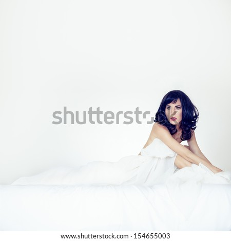 Fashion portrait of a sensual girl in white bed - stock photo