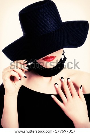 Fashion portrait of a woman with nail art, black hat and red lips. Vintage retro Paris style.  - stock photo