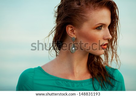 Fashion portrait of a young model with wet long ginger (red) hair in blue dress posing at the seaside. Perfect skin and make-up. Profile. Close up. Copy-space. Outdoor shot - stock photo
