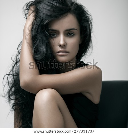 Fashion portrait of a young sensual beautiful brunette model with long black straight hair. Smoky eyes. - stock photo