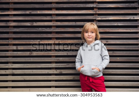 Fashion portrait of adorable toddler boy wearing grey sweatshirt and red trainings, standing against wooden background - stock photo