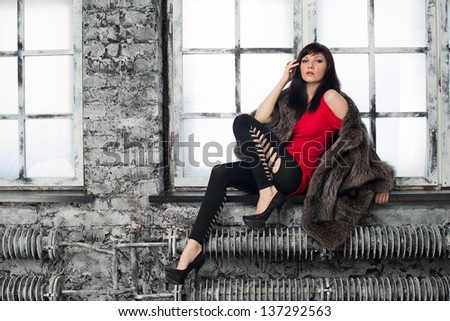 Fashion portrait of attractive caucasian female wearing fur coat and posing on a window sill, horizontal shot - stock photo